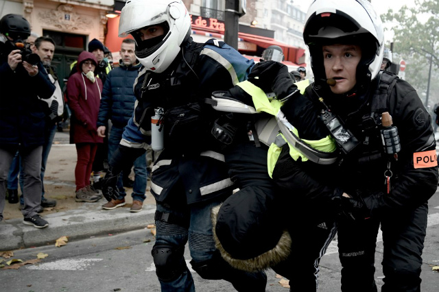 CLASH. Police officers detain a man during clashes with protesters on November 16, 2019 near Place d'Italie in Paris, on the sidelines of a demonstration of the yellow vest (gilets jaunes) marking the first anniversary of the movement. Photo by Philippe Lopez/AFP