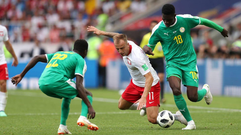 BEREBUT BOLA. Pertarungan sengit antara timnas Polandia dan Senegal berbuah kemenangan Senegal. Foto dari FIFA.com