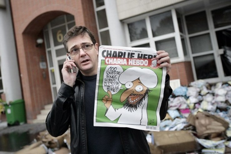 CONTROVERSIAL PHOTO. Some news organizations decided to blur the magazine cover in this photo. Charlie Hebdo's slain publisher known as Charb, uses his cell phone as he shows a special edition of French satirical magazine on November 2, 2011 in Paris. The cover features a cartoon of a grinning, bearded figure, saying: u2018100 lashes if you don't die of laughter!u2019 File photo by Alexander Klein/AFP