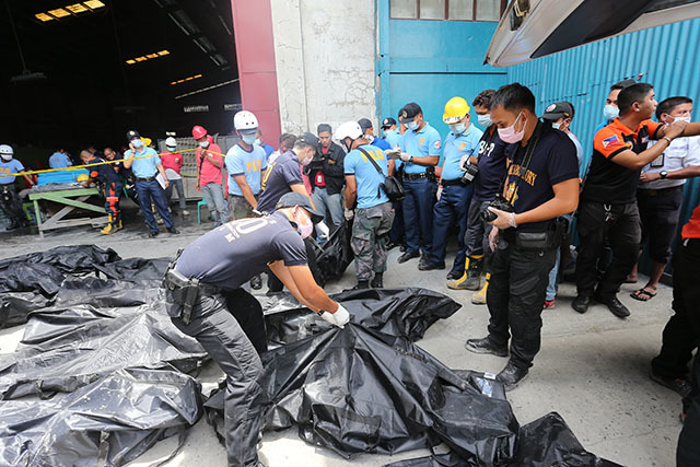 FATALITIES. Authorities seal the remains of workers killed in a footwear factory in Valenzuela. Photo by PNP-PIO