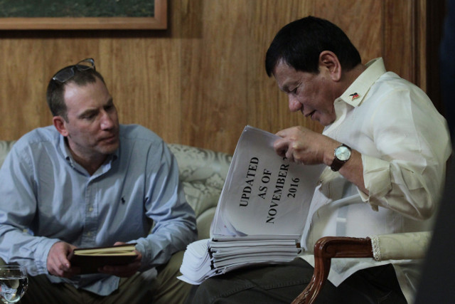 SHOW AND TELL. President Rodrigo Duterte shows Ioan Grillo his thick list of suspected drug personalities, a document no Filipino journalist has seen up close. Photo by King Rodriguez/Presidential Photo