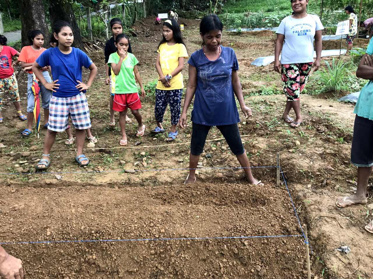 READY. A group of Mangyan mothers gather around to prepare the mound of land for planting. Photo from ZEP 2030