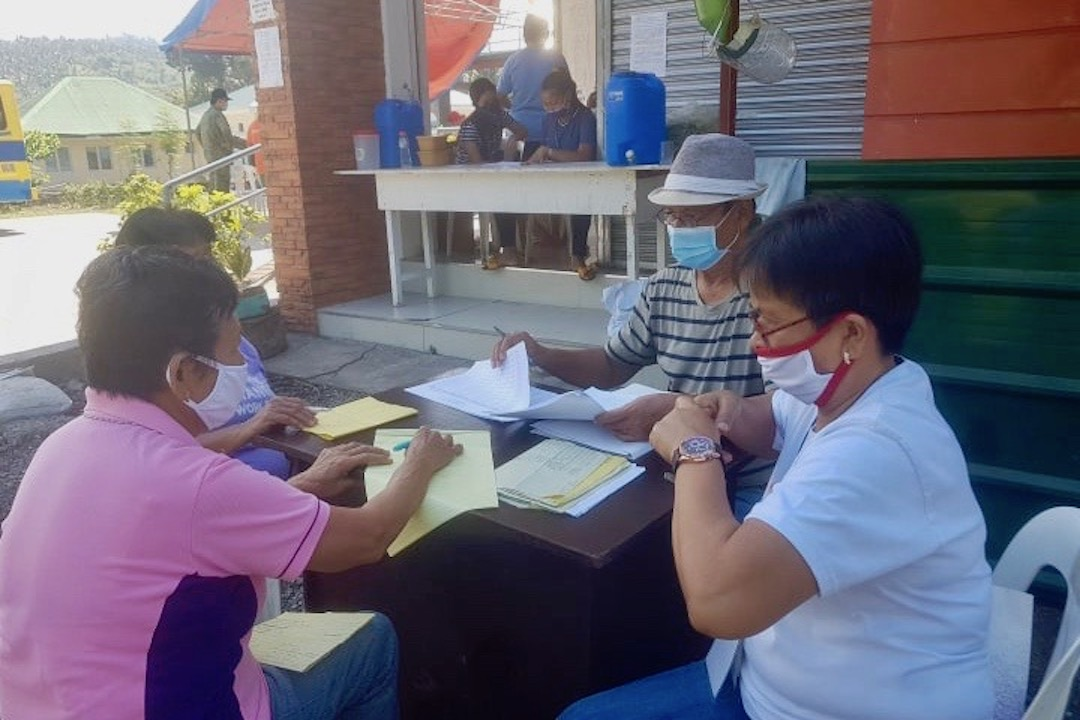 WORK OUTSIDE. Barangay officials of Buluang, Baao, Camarines Sur work outside to validate paperwork for their social relief efforts. Photo from Alan Bolo