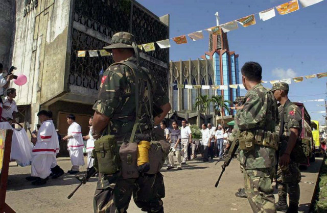 THREATS. Army soldiers guard a Christian procession marking the anniversary of the Jolo's Mount Carmel Cathedral in the aftermath of attacks in 2000. Photo by Romeo Gacad/AFP