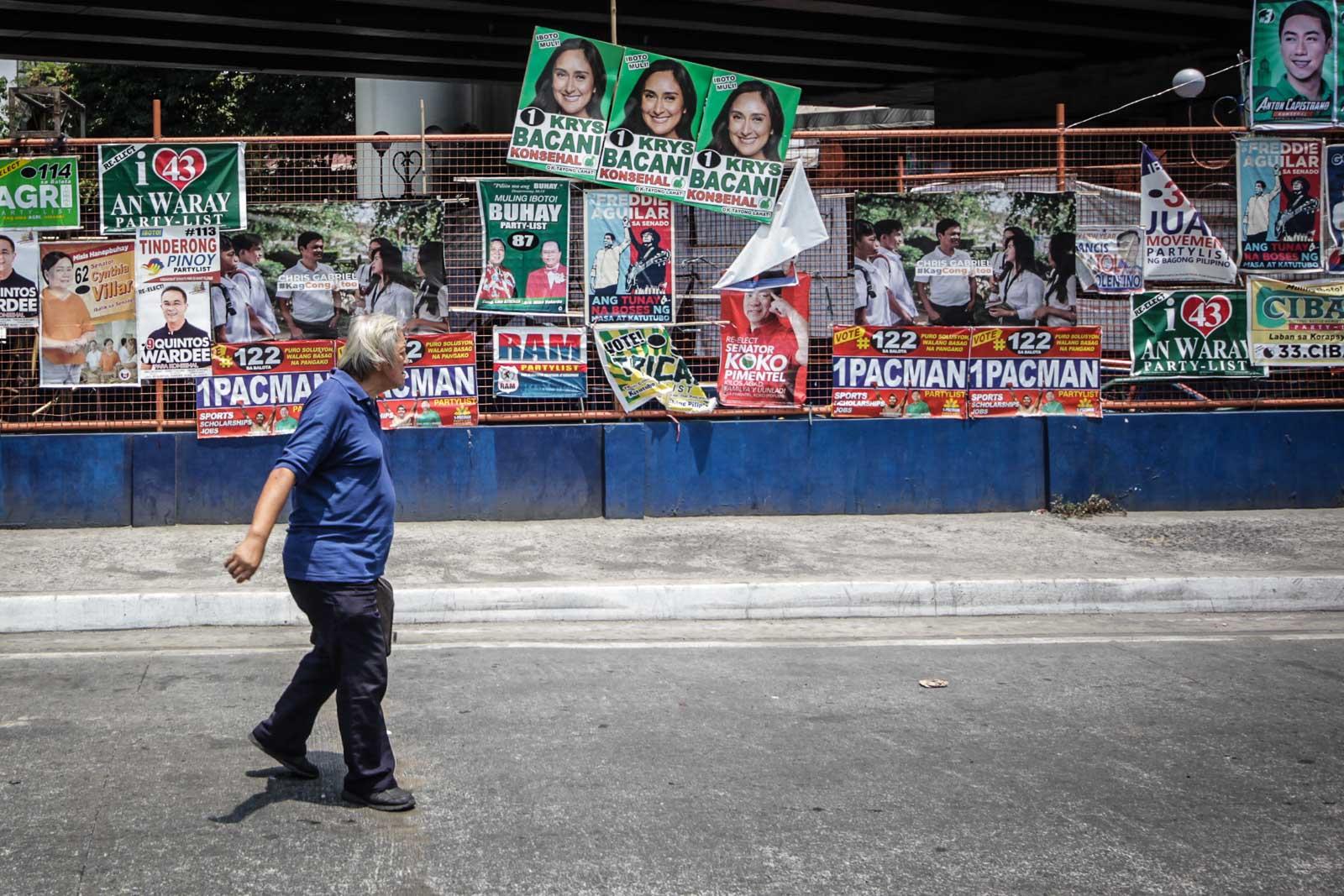A man walks past through the political poster along Legarda extension in Manila on March 30, 2019. Photo by Lito Borras/Rappler