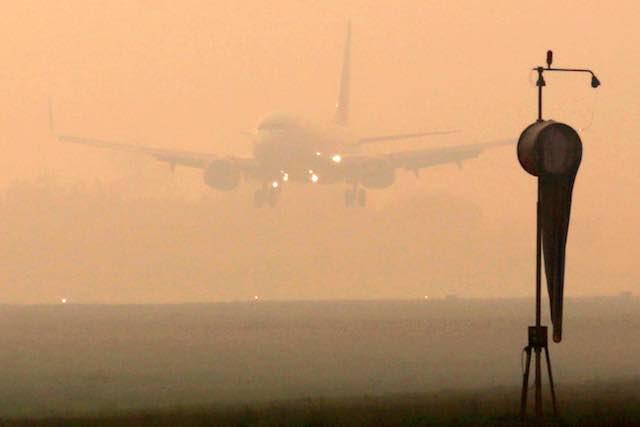 ASAP. Pesawat mendarat di tengah kabut asap yang menutupi Bandara Sultan Mahmud Badaruddin II di Palembang, Sumatera Utara, 29 Agustus 2015. Foto oleh Tamy Utari/EPA