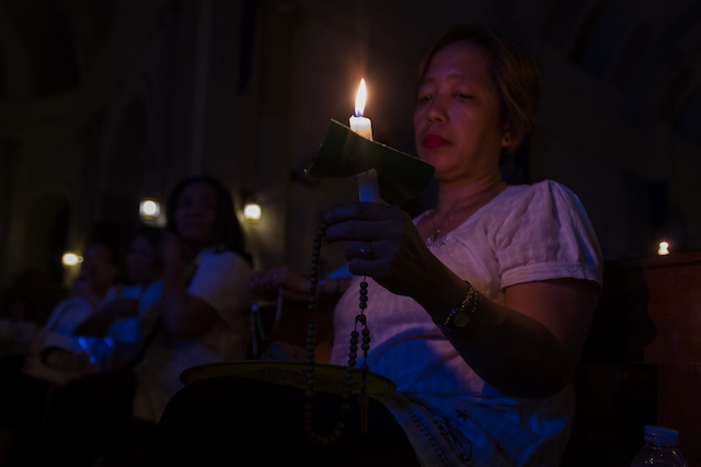 CANDLE-LIT MASS. Mass-goers hold candles inside the Malate Church as they observe Earth Hour. Photo by Maria Tan/Rappler