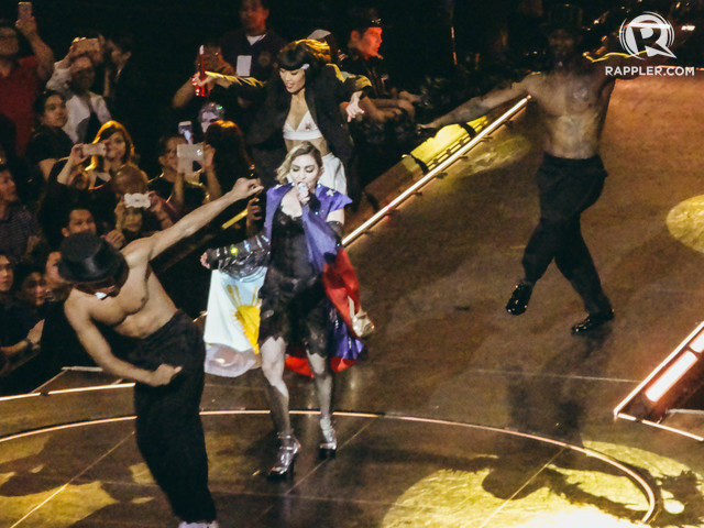 DRAPED. Pop star Madonna wears the Philippine flag as a cape in this part of her performance in Manila. Photo by Nicole Reyes/Rappler