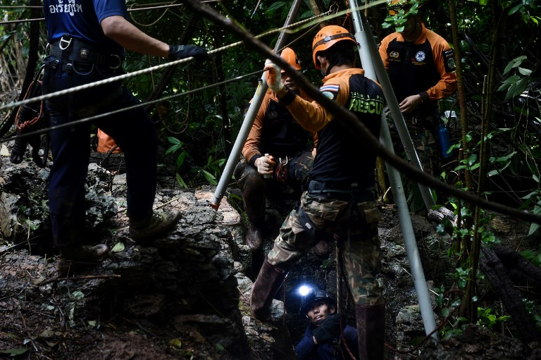 RESCUE. Thai rescue specialists (in orange) help a Thai Airforce soldier descent into a possible opening to the Tham Luang cave, at the Khun Nam Nang Non Forest Park in Chiang Rai province on June 30, 2018 as the rescue operation continues for the children of a football team and their coach. Photo by Lillian Suwanrumpha/AFP