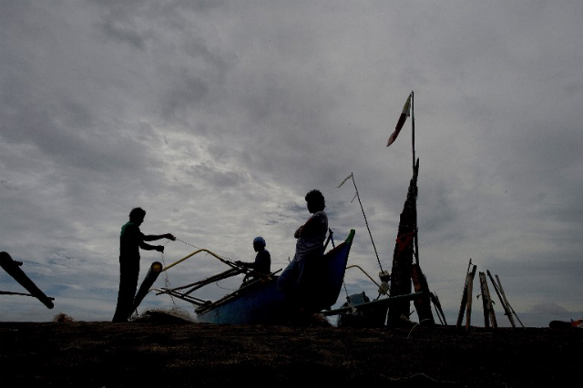 WORK NEEDED. Fishermen prepare their fishing net along a shore in Tacloban on the eastern island of Leyte on October 16, 2014. Tacloban was devastated by Super Typhoon Yolanda (Haiyan) on November 8, 2013. File photo by Noel Celis/AFP