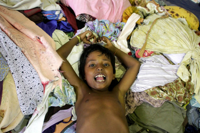 CLOTHES, FINALLY. A Rohingya child lies among the used clothes donated by the local people at Lhok Sukon stadium, North Aceh, Indonesia, 12 May 2015. More women and children take the risk to go out to sea to find better life outside of Myanmar. File photo by Zikri Maulana/EPA
