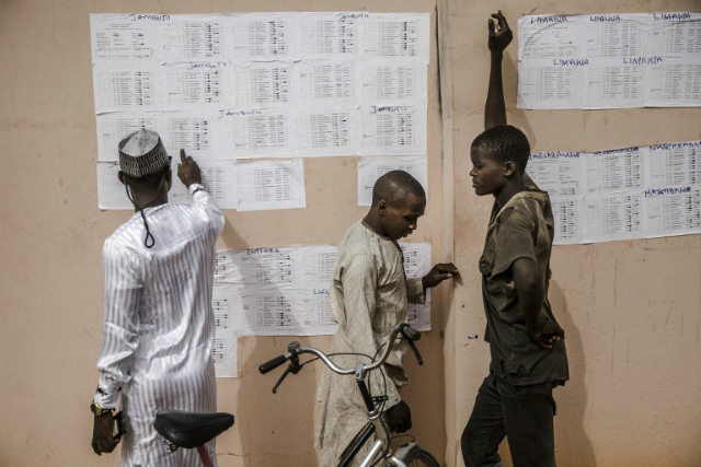 POSTPONED. People check their names in voting lists at the State INEC Independent Electoral Comission Office in Jimeta on February 16, 2019. File photo by Luis Tato/AFP