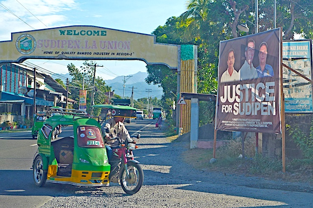 SUPIDEN. A poster with the image of the late mayor Alexander Buquing flanked by his driver and bodyguard, all killed in an ambush in October 1, stands near the welcome arch of Supiden town