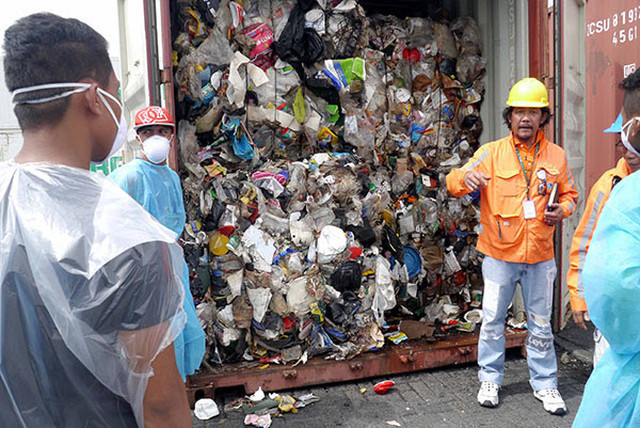 ILLEGAL GARBAGE. Geri Sau00f1ez of DENR-EMB opens one of the 103 container vans of trash shipped from Canada. Photo courtesy of BAN Toxics