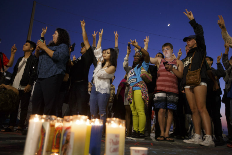 VIGIL. Protesters raise their hands with peace signs to call for peace after a string of nationwide police shootings and the slaying of police officers in Dallas, Texas during a vigil in Huntington Beach, California, USA, 08 July 2016. Photo by Eugene Garcia/ EPA