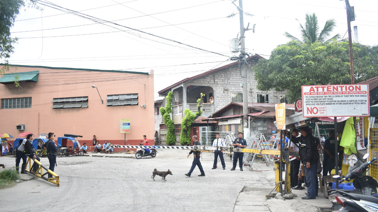 GUARDED. Police (not in photo) and security personnel man the entrance of NutriAsia factory in Marilao.