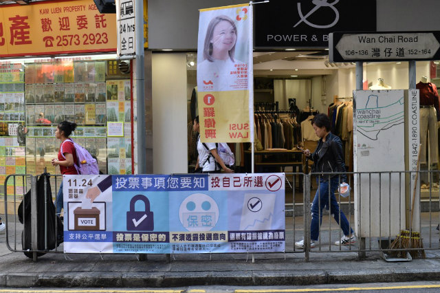 IMPORTANT. Pedestrians walk past a banner for Hong Kong's district elections, scheduled to take place on November 24, in the Wanchai district of Hong Kong on November 22, 2019. Photo by Nicolas Asfouri/AFP