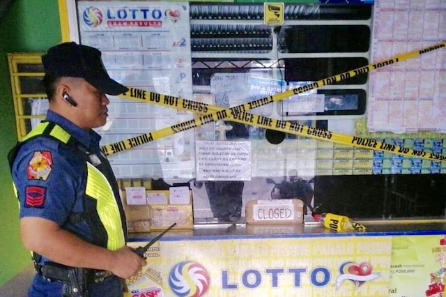 CLOSED. A cop oversees the closure of a lottery outlet in Makati City. NCRPO photo