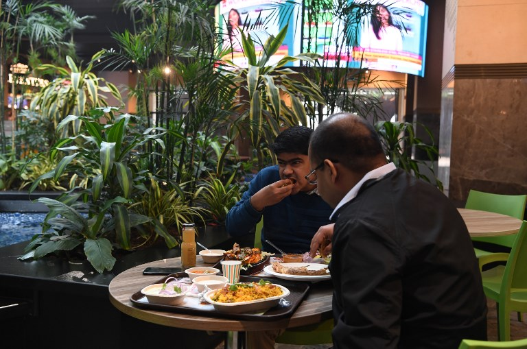 RICH DELHI. This photograph taken on February 6, 2019 shows visitors eating at The Walk food courtyard, a space designed with green spaces and artificial water bodies to help filter out unhealthy air pollution, in New Delhi. Photo by Sajjad Hussain/AFP