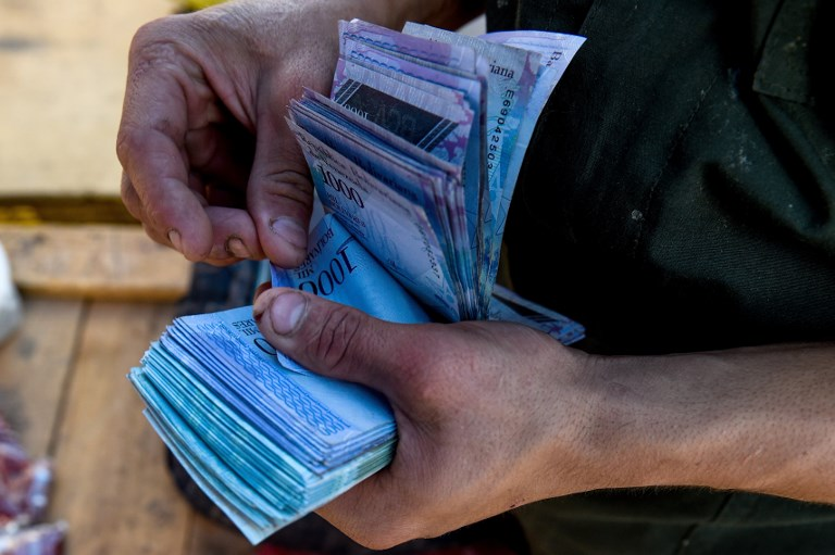 HYPERINFLATION. A man counts 1000-Bolivar-bills to buy groceries at the municipal market of Coche, a neighborhood of Caracas, on June 20, 2018. File photo by Federico Parra/AFP