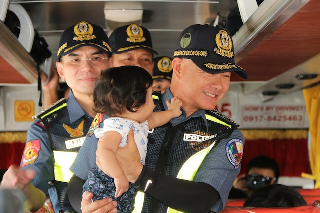 PHOTO OP. Albayalde carries the baby of a passenger during the inspection. PNP photo