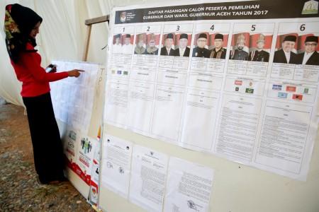 Warga melihat Daftar Pemilih Tetap (DPT) yang ditempel di Tempat Pemungutan Suara (TPS) di Desa Pango Raya, Banda Aceh, Aceh, Selasa (14/2). Foto oleh Irwansyah Putra/ANTARA