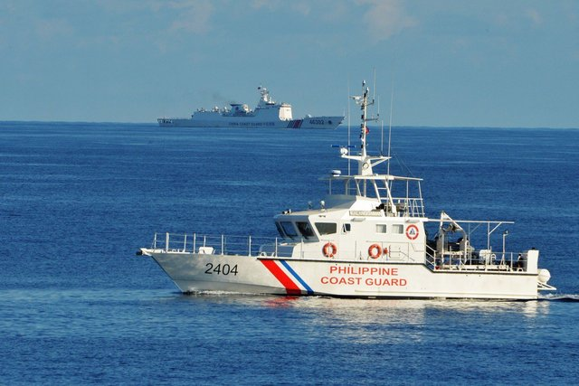 WEST PHILIPPINE SEA. A Philippine Coast Guard ship (R) sails past a Chinese Coast Guard ship during a joint search and rescue exercise between Philippine and US coast guards near Scarborough Shoal. Photo by Ted Aljibe/AFP