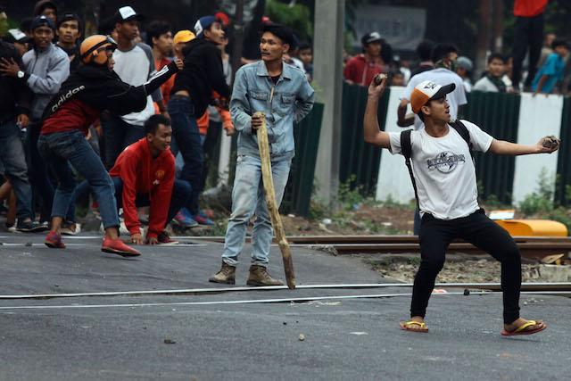 RUSUH JAKMANIA. Pendukung Jakmania melempar batu ke arah polisi yang sedang berjaga di Stadion Gelora Bung Karno, Minggu, 18 Oktober 2015. Foto oleh Rappler