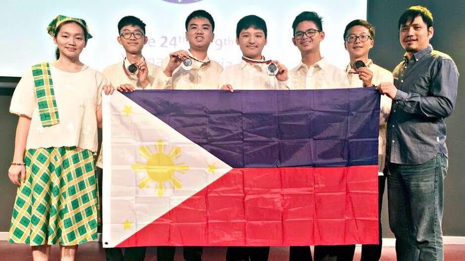 Philippine team members show the flag and their medals at the awarding ceremony of the 21st Junior Balkan Mathematical Olympiad (JBMO) in Bulgaria. They are (from left) coach Hazel Joy Shi, Immanuel Josiah Balete, Vincent Dela Cruz, Bryce Ainsley Sanchez, Aiman Andrei Kue, Eion Nikolai Chua and coach James Kelvin Martin. (Photo by MTG)