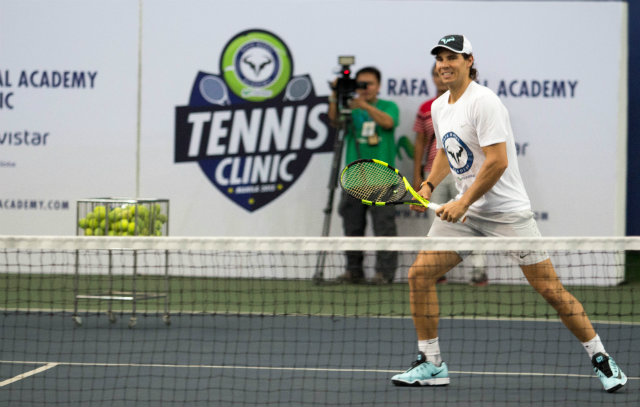 Rafael Nadal smiles as he plays tennis with young Filipinos. Photo by Ena Terol/Rappler