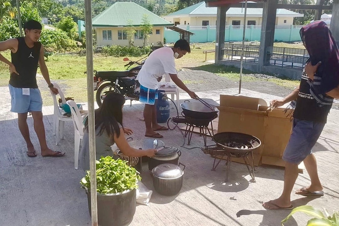 COMMUNITY KITCHEN. Barangay Buluang staffers cook for their constituents. Photo from Alan Bolo