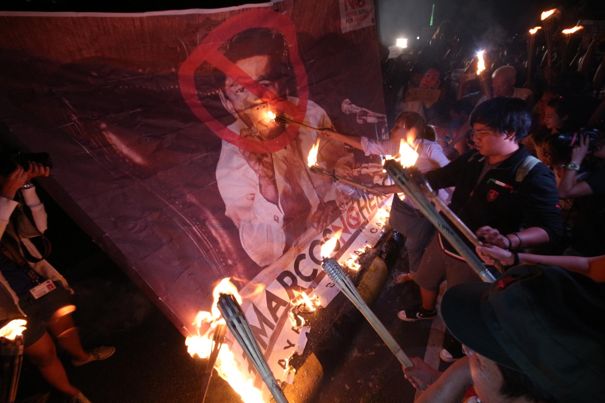 NEVER AGAIN. UP students and Martial Law victims torch a large picture of the late dictator Ferdinand Marcos in a protest rally at the UP compound to condemn the Supreme Court's decision granting hero's burial of in the Libingan ng mga Bayani. Photo by Joel Liporada/ Rappler
