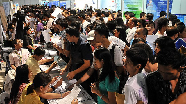 JOB HUNTERS. Aspiring employees submit their applications at a job fair. File photo by Ted Aljibe/AFP
