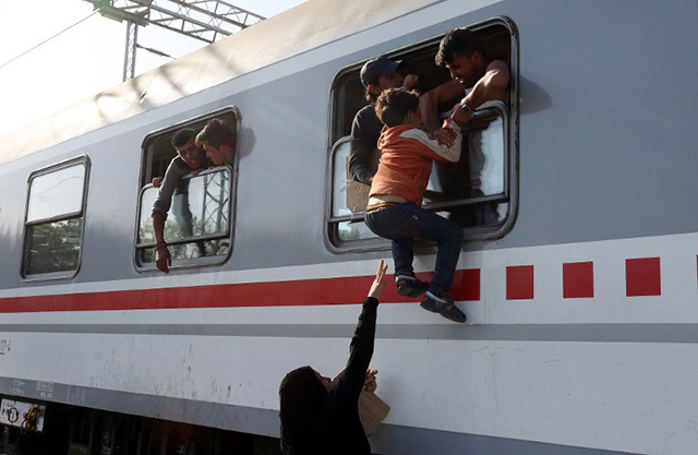 STRUGGLE. Migrants board through a window a train heading to Zagreb at a railway station, near the official border crossing between Croatia and Serbia, near the eastern-Croatian town of Tovarnik, on September 18, 2015. AFP photo
