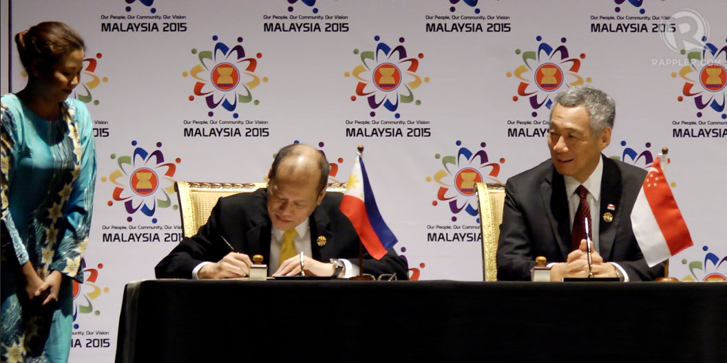 TAKING TURNS. Philippine President Benigno Aquino III signs the ASEAN Declaration on the Establishment of the ASEAN Community. Looking on is Singapore Prime Minister Lee Hsien Loong.