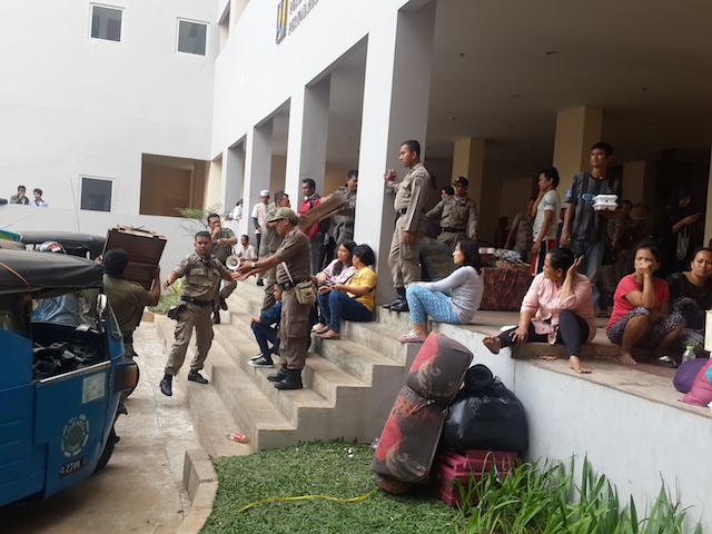 Sastpol PP mengawasi warga Kampung Pulo yang dipindahkan ke rusunawa Jatinegara Barat, Jakarta Timur. Foto oleh Uni Lubis