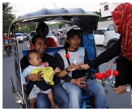 Mahasiswi Universitas Islam Negeri (UIN) Makassar (kiri) membagikan bunga kepada seorang ibu yang melintas di Jalan Andi Pangeran Pettarani, Makassar, Sulawesi Selatan. UIN Makassar telah memberikan beasiswa kepada penghafal Alrquran selama 5 tahun terakhir. Foto oleh Antara//Abriawan Abhe