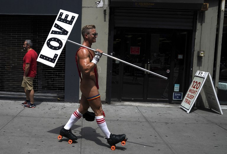 LOVE. People take part in the annual 2018 New York City Pride Parade on June 24, 2018 as they make their way down 7th Avenue in New York. Photo by Timothy A. Clary/AFP