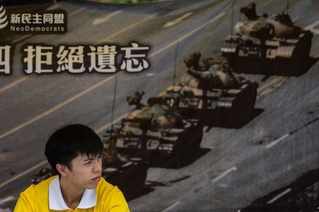 MORE KILLED? An activist sits in front of a poster of the 'Tank Man' a popular figure related to the bloody Tiananmen Square crackdown in 1989. File photo by Anthony Wallace/ AFP