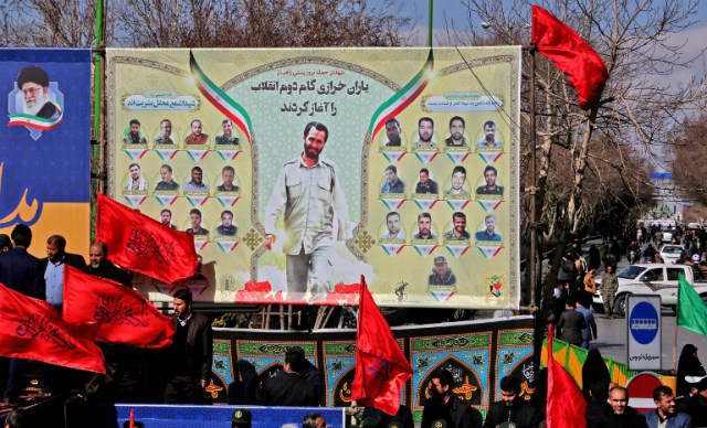 JUSTICE. Iranian mourners gather under a banner bearing portraits of members of Revolutionary Guards who were killed in a suicide attack in February 13. Photo by Atta Kenare/AFP