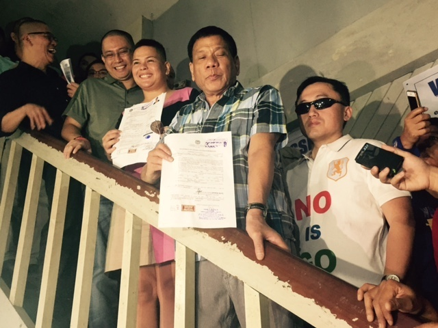 COC FOR PRESIDENT. Davao City Mayor Rodrigo Duterte (second from right) and Sara Duterte-Carpio hold up their certificates of candidacy for president and mayor, respectively, on November 27, 2015. Photo by Editha Caduaya/Rappler