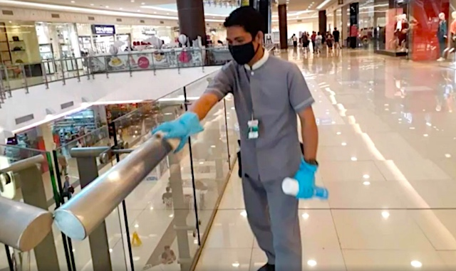 PRECAUTIONARY MEASURE. An employee of Robinsons Malls sanitizes the railing as a preventive measure against the spread of the novel coronavirus. Screenshot from Robinsons Malls video