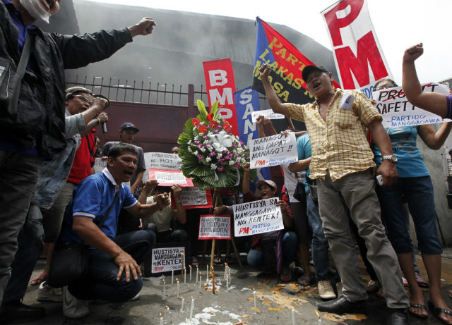 PROTEST. Filipino workers offer flowers as they stage a demonstration at the gate of a burnt footwear factory in Valenzuela city, east of Manila, Philippines, May 15 2015. Photo by Francis R. Malasig/EPA