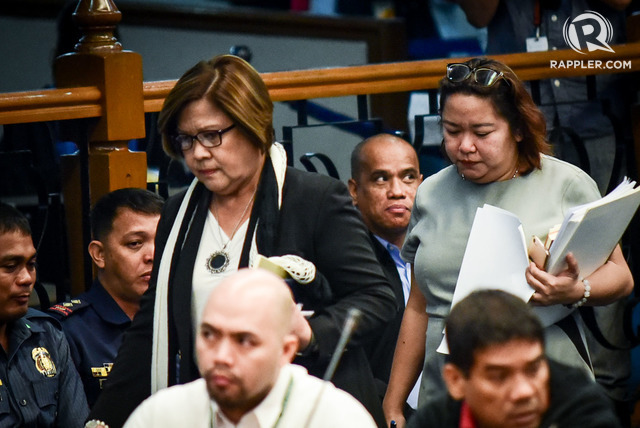 NO REGRETS. Senator Leila de Lima is seen in this photo walking past her former bodyguard and boyfriend Ronnie Dayan (lower right) at a Senate hearing. File photo
