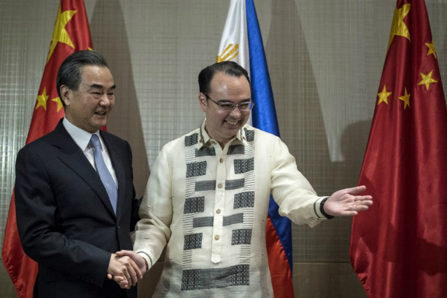 TOP DIPLOMATS. Chinese Foreign Minister Wang Yi (L) shakes hands with Philippine Foreign Secretary Alan Peter Cayetano (R) after signing the guestbook in Manila on July 25, 2017. Photo by Noel Celis/AFP