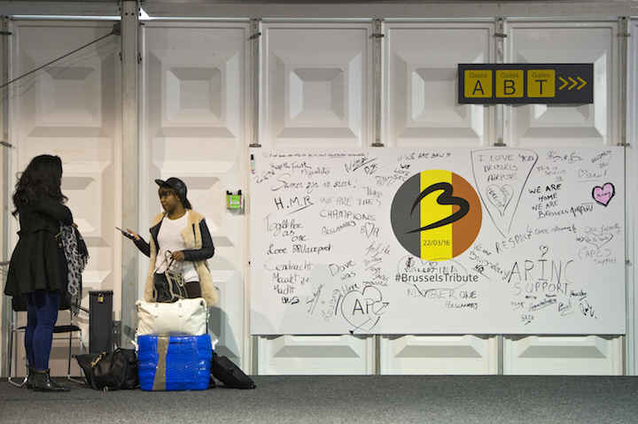 REOPENING. Passengers stand next to messages in tribute to the 22 March terror attacks victims at a provisional airport building at Brussels Airport, Belgium. Photo by Laurie Dieffembacq/EPA