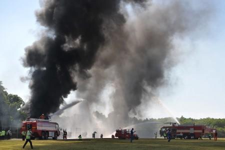 Sejumlah petugas pemadam kebakaran berupaya memadamkan api saat simulasi kecelakaan pesawat di Bandara Ngurah Rai, Bali, Selasa (18/10).Foto oleh Nyoman Budhiana/ANTARA