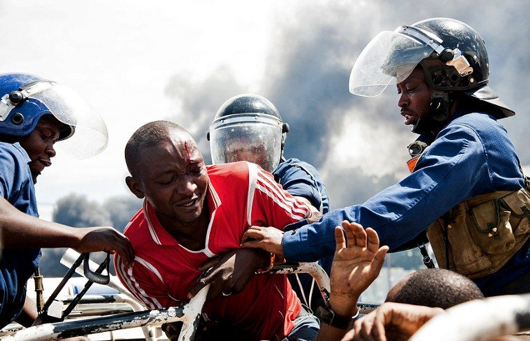 PROTEST. A man is lifted by police during a protest in Bujumbura on May 13, 2015. A top Burundian general announced today the overthrow of President Pierre Nkurunziza, following weeks of violent protests against the president's bid to stand for a third term. Photo by Landry Nshimiye / AFP