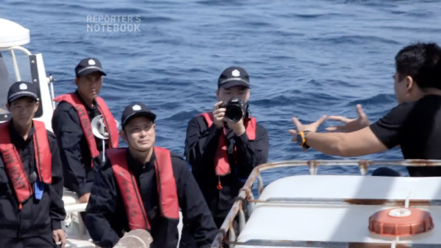 TENSE ENCOUNTER. Filipino journalist Jun Veneracion (right) of GMA-7 is driven away from Panatag Shoal (Scarborough Shoal) by members of the Chinese Coast Guard. Screenshot from Facebook video of GMA-7's Reporter's Notebook