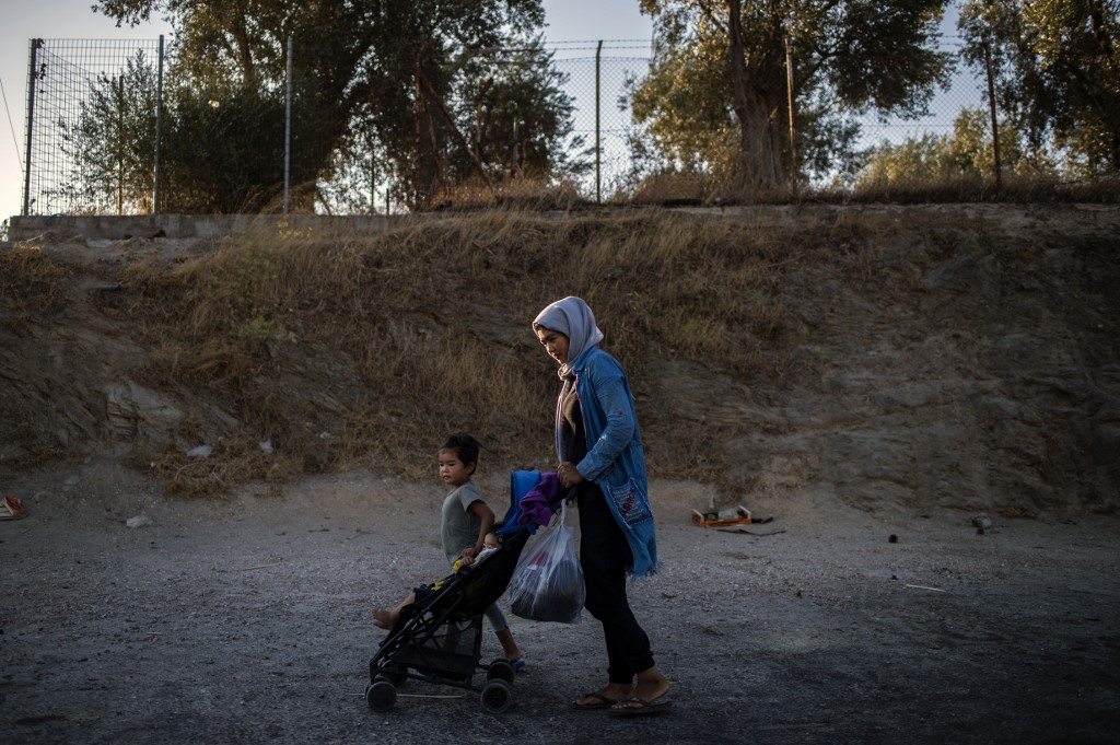 MIGRANT CRISIS. A migrant woman walks with her children outside the official refugee camp of Moria on the Greek island of Lesbos, on August 31, 2019. Photo by Angelos Tzortzinis/AFP